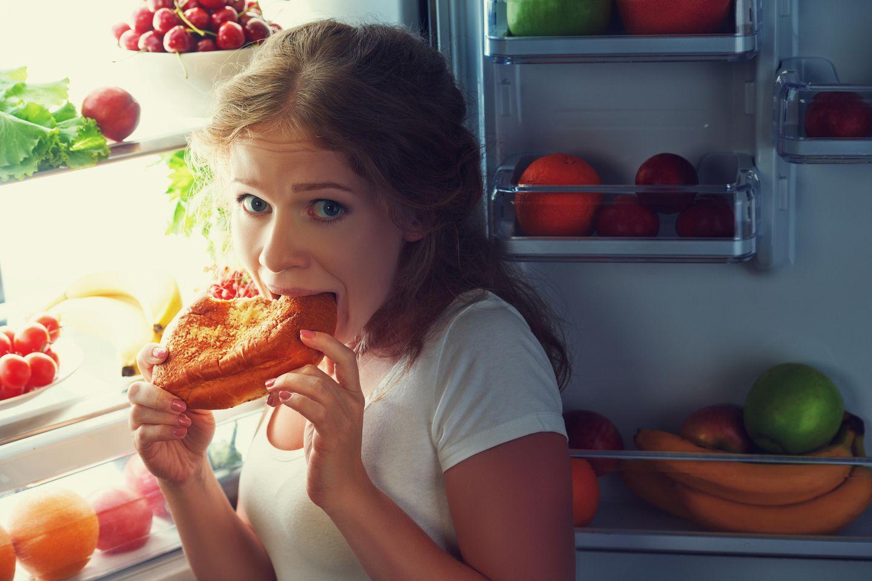 Abnehmen ohne Hunger: Frau isst heimlich Fast Food