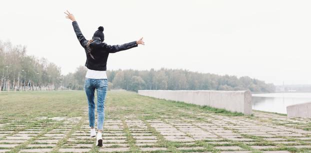 Einsamkeit überwinden: Eine Frau springt allein über eine einsame Fläche
