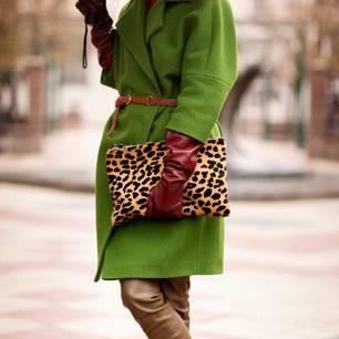 Herbst-Accessoires: Frau mit grünem Mantel und Leo-Tasche