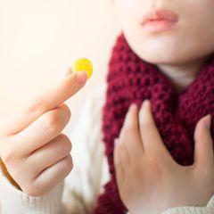 Ständig Halsschmerzen – Frau mit Halsweh und Bonbon in der Hand