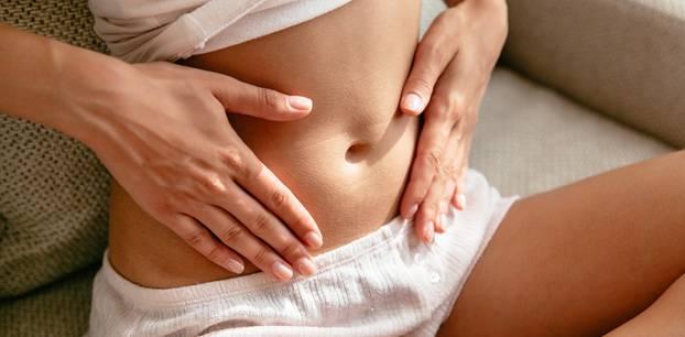 Schwangerschaftsanzeichen: Frau sitzend, Hände auf Bauch