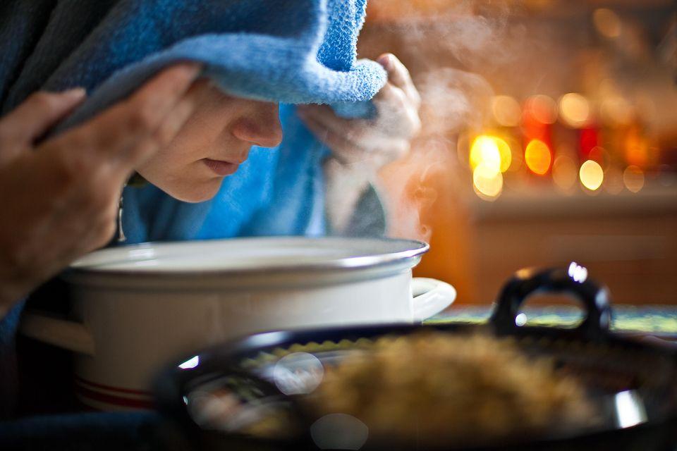 Grippe-Behandlung:  Frau inhaliert