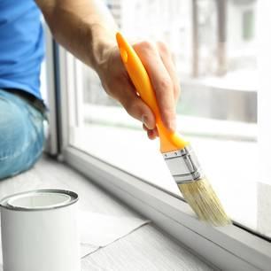 Fenster streichen: Mann streicht Fenster mit Pinsel