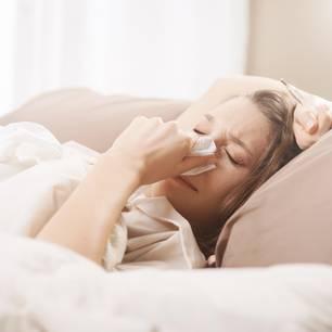 Grippe Dauer: Frau liegt krank im Bett