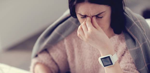 Grippe Symptome: Frau hat Fieber und Kopfweh