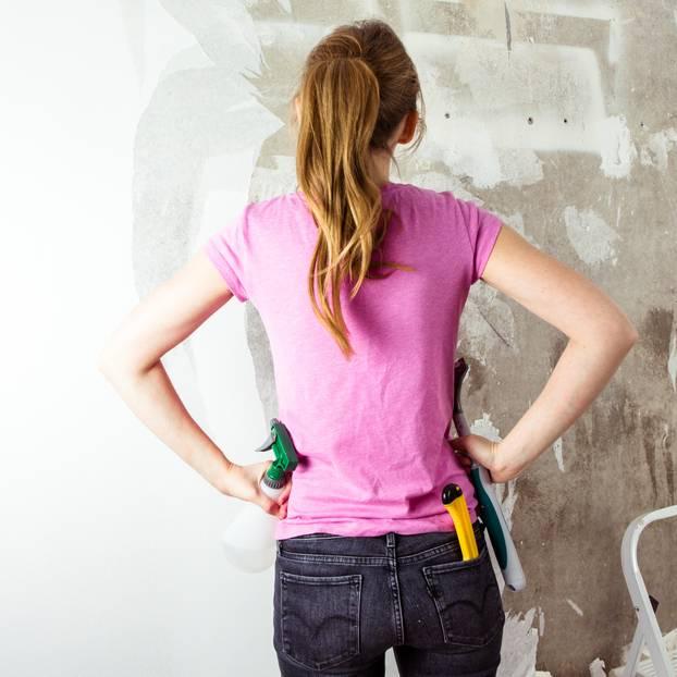 Tapete entsorgen: Frau betrachtet zu tapezierende Wand