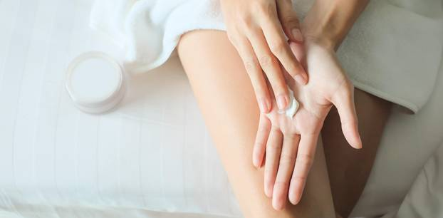 Handcreme selber machen: Frau cremt sich Hände ein