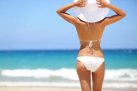 Bikinifigur: Frau steht im Bikini am Strand