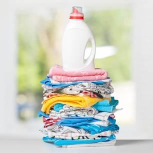 Waschmittel selber machen: Waschmittelflasche steht auf einem Berg von Wäsche