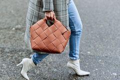 Herbst-Must-haves: Frau mit Karo-Mantel, weißen Stiefeletten und brauner Tasche