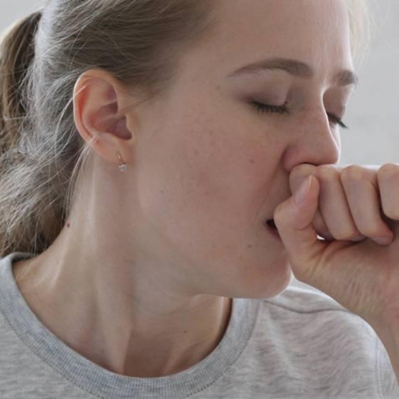 Hustenreiz: Frau hustet mit Hand vor dem Mund