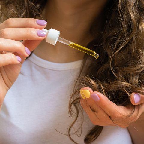 Rizinusöl Anwendung: Frau trägt Öl auf Haare auf