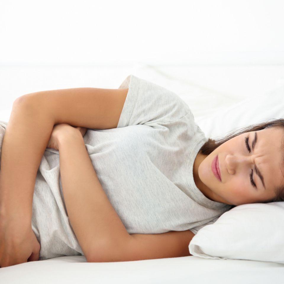 Was hilft gegen Durchfall? Frau liegt im Bett und hält sich den Bauch