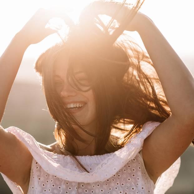 Fliegende Haare: Fraue mit fliegenden Haaren lacht