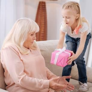 Geschenke für Oma: Enkelin beschenkt Oma auf dem Sofa