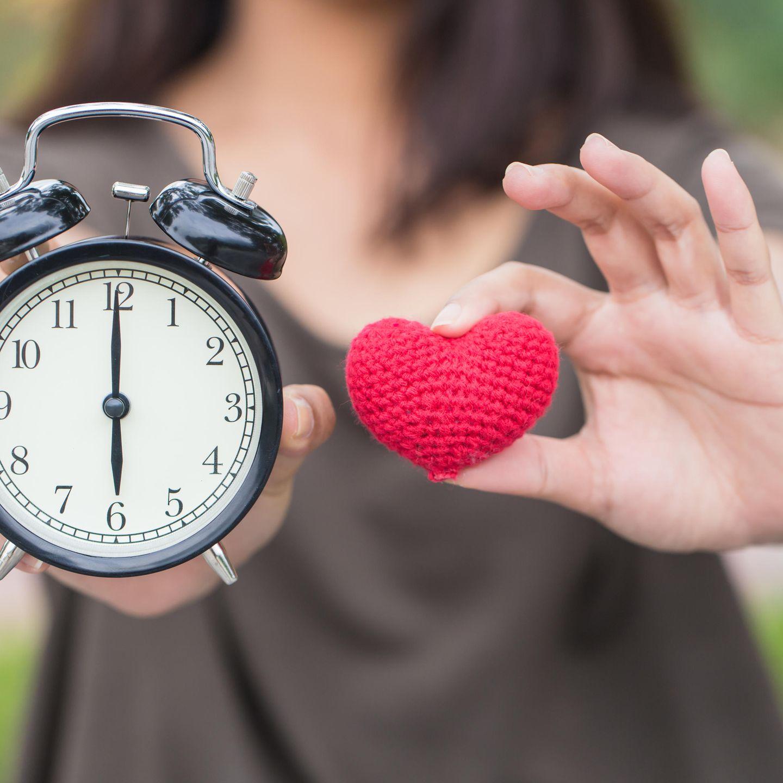 Zeit schenken: Frau mit Herz und Uhr in den Händen