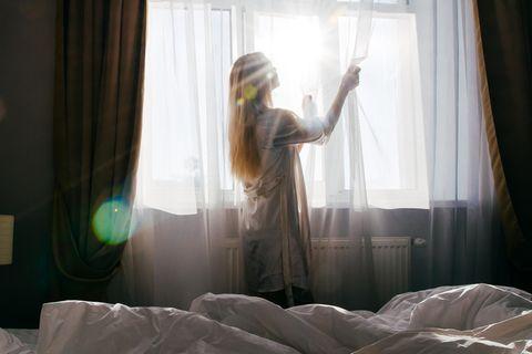 Ist das Hotelzimmer sauber: Frau schiebt Vorhänge zur Seite