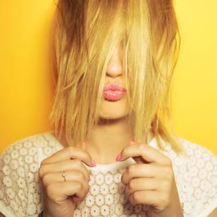 Gelbstich im Blond: Frau mit gelben Haaren macht Kussmund