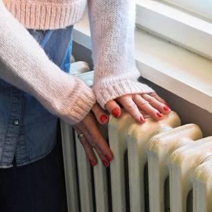 Schlafzimmer heizen: Frau berührt die Heizung