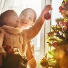 Weihnachtsbaum aufstellen: Mutter und Tochter hängen Kugeln an den Baum