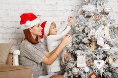 Weihnachtsbaum schmücken: Mutter und Tochter schmücken den Baum