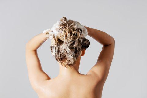 Haare mit Heilerde waschen: Frau wäscht Haare mit Shampoo
