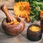Hämorrhoiden: Schale mit Mörser, Creme aus Calendula im Tiegel und kleines Fläschchen daneben