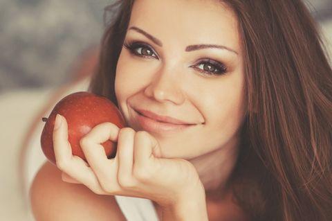 Apfelessig für die Haut: Frau mit einem Apfel in der Hand