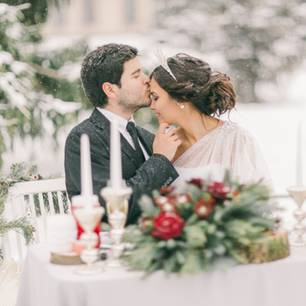 Winterhochzeit - Tipps für deinen Traum in Weiß: Brautpaar sitzt draussen bei Schnee am geschmückten Tisch, er küsst sie auf