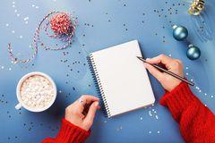 Was kann ich mir zu Weihnachten wünschen: Frau legt sich Wunschzettel an