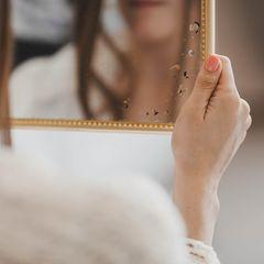 Angst vor sich selbst: Frau, die Spiegel vor sich hält