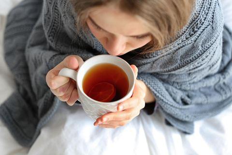 Hausmittel bei Blasenentzündung: Frau in Decke eingehüllt trinkt eine Tasse Tee