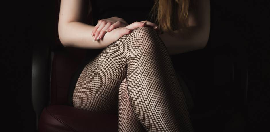 BDSM-Paartherapie: Frau mit Netzstrumpfhose sitzend