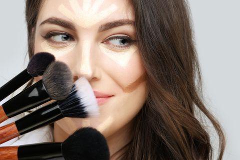 Gesicht schmaler schminken: Frau mit Contouring im Gesicht und Pinsel in der Hand
