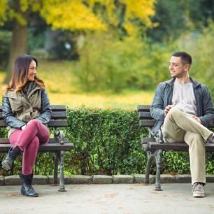 Frauen ansprechen: Ein Mann und eine Frau sitzen auf zwei Parkbänken und schauen sich an