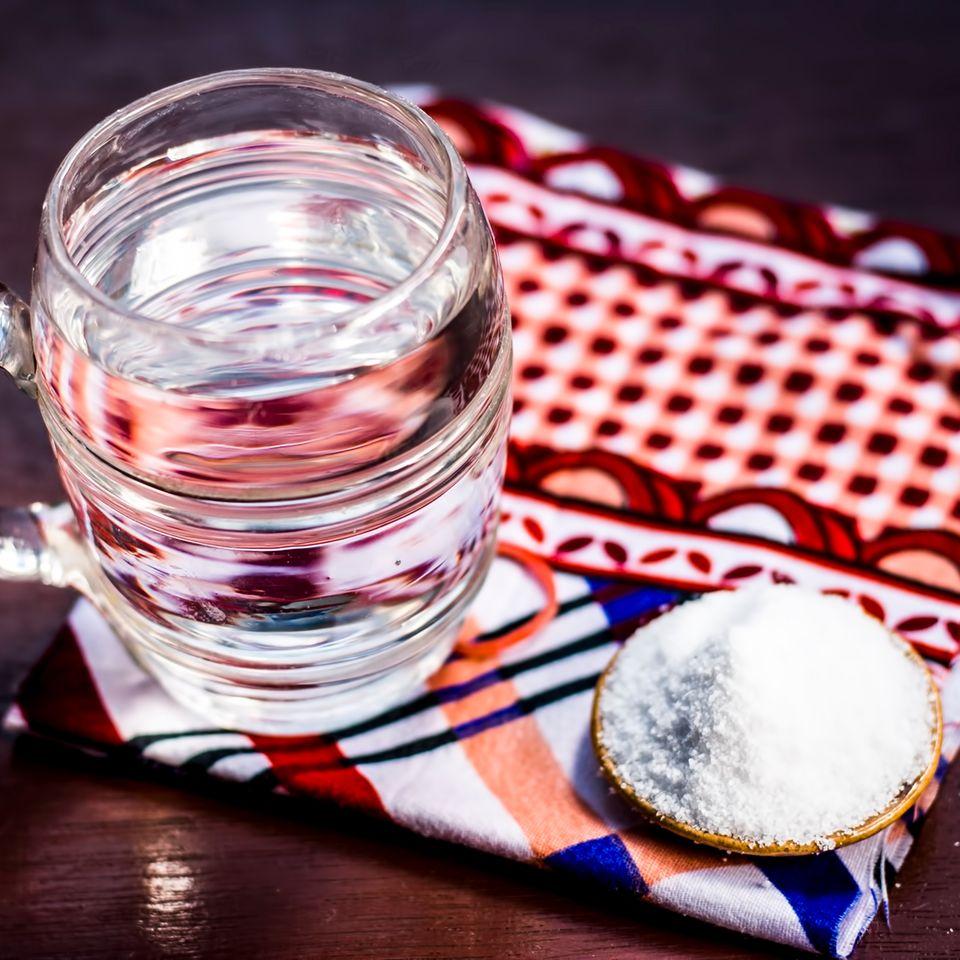 Hausmittel gegen Sodbrennen: Das sind die besten: Glas Wasser auf einem bunten Tuch, daneben eine Schale mit hellem Pulver