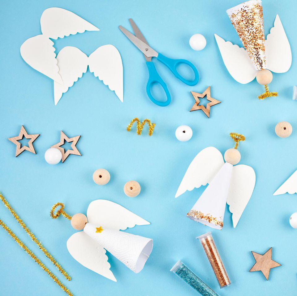 Engel basteln: die schönsten Ideen und Anleitungen - viele Bastelutensilien auf hellblauem Untergrund