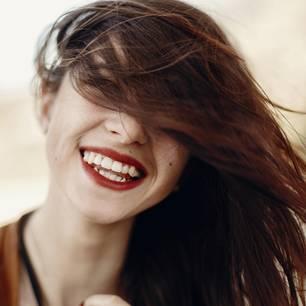 Vitamine für die Haare: Lachende Frau mit langen, gesunden Haaren