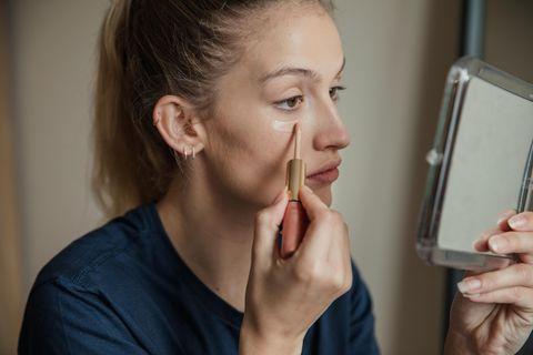 Concealer: Frau benutzt Concealer unter den Augen