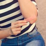 Schürfwunde – wie du sie richtig behandelst: Frau klebt ein Pflaster auf ihren Unterarm