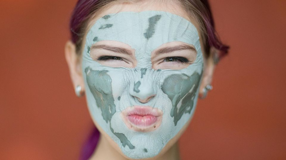 Skin Gritting: Frau mit Maske aus Tonerde im Gesicht