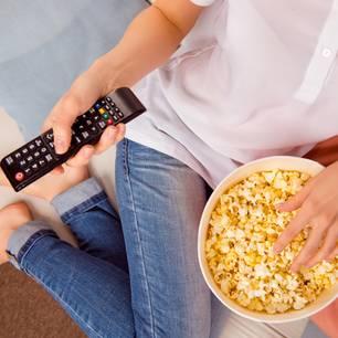 Horrorfilme anschauen verbrennt laut Studie Kalorien: Frau mit Fernbedienung und Popcorn