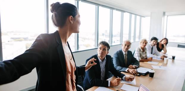 Assessment Center: Das kommt auf dich zu: Frau steht im Konferenz am Kopfende des Tisches und hält eine Rede