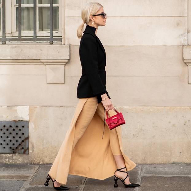 Handtaschen-Trends 2019: Caro Daur mit roter Mini-Tasche, schwarzem Rollkragenpullover und einem Rock mit Beinschlitz