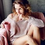Signale, dass wir eine Vorstellung lieben: Verträumte Frau schaut aus dem Fenster
