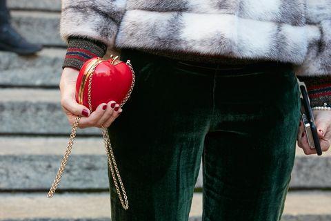 Herbsttrend Samt: Frau mit Samthose und roter Apfel-Tasche