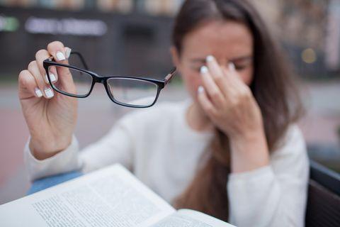 Augenzucken: Das kannst du tun: Frau fasst sich mit der Hand an die Augen und hält rechts die Brille