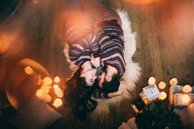 5 Sprachen der Liebe: Pärchen liegt bei Kerzenlicht zusammen auf einem Kunsthaar-Tierfell