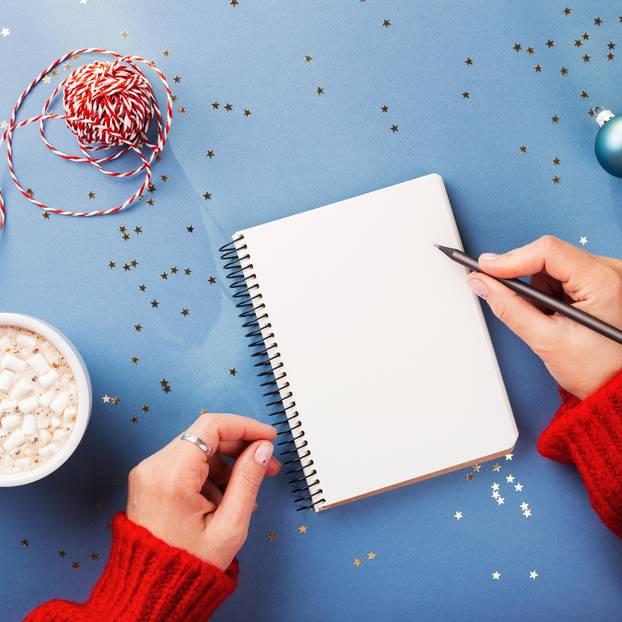 Wunschzettel schreiben: Frau schreibt in Notizblock