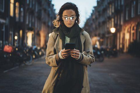 Digitale Abhängigkeit: Frau steht auf einer Straße und schaut auf ihr Handy